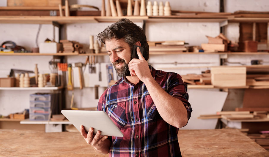 Man with beard in woodwork studio using phone and tablet